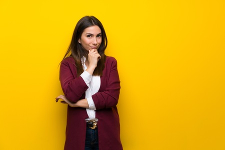 Young woman over yellow wall thinking
