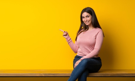 Young woman sitting on table pointing finger to the side