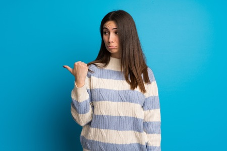 Young woman over blue wall unhappy and pointing to the side
