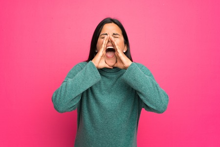 Young Colombian girl with green sweater shouting and announcing something