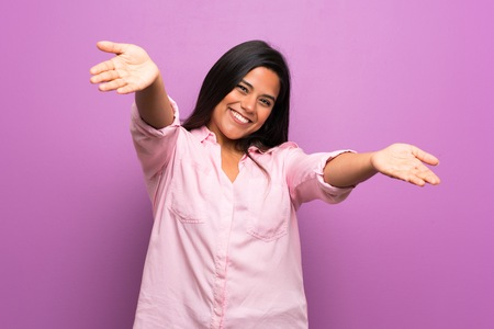 Young Colombian girl over purple wall presenting and inviting to come with hand Banco de Imagens