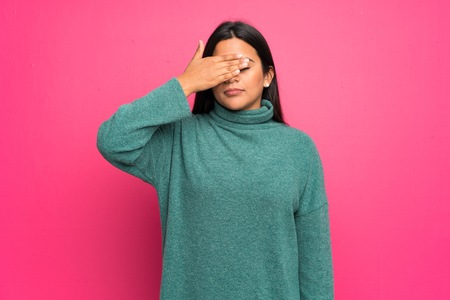 Young Colombian girl with green sweater covering eyes by hands. Do not want to see something