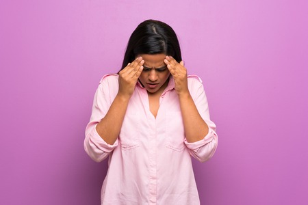 Young Colombian girl over purple wall with tired and sick expression