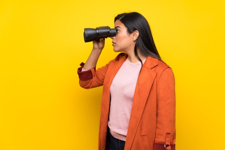 Young Colombian girl over yellow wall and looking in the distance with binoculars Stok Fotoğraf