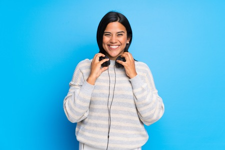 Young Colombian girl with sweater with headphones