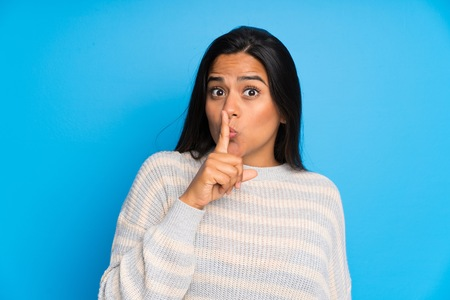 Young Colombian girl with sweater doing silence gesture
