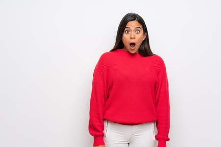 Young Colombian girl with red sweater with surprise facial expression