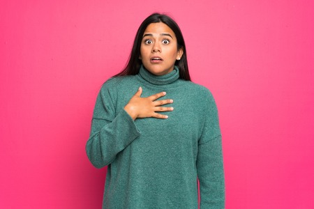 Young Colombian girl with green sweater surprised and shocked while looking right