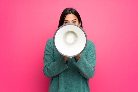 Jong Colombiaans meisje met groene trui die door een megafoon schreeuwt Stockfoto