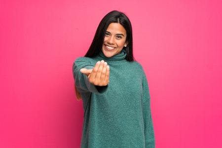 Giovane ragazza colombiana con un maglione verde che invita a venire con la mano. Felice che tu sia venuto