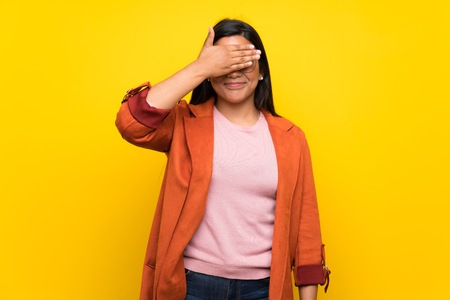 Young Colombian girl over yellow wall covering eyes by hands. Do not want to see something