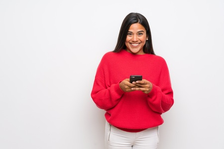 Young Colombian girl with red sweater sending a message with the mobile