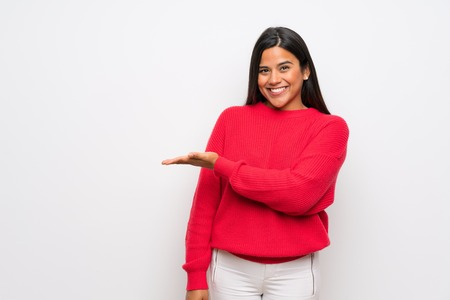 Young Colombian girl with red sweater presenting an idea while looking smiling towards Banco de Imagens