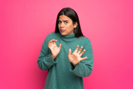 Young Colombian girl with green sweater nervous stretching hands to the front