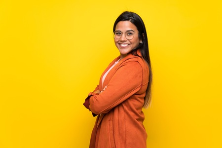 Young Colombian girl over yellow wall with arms crossed 版權商用圖片