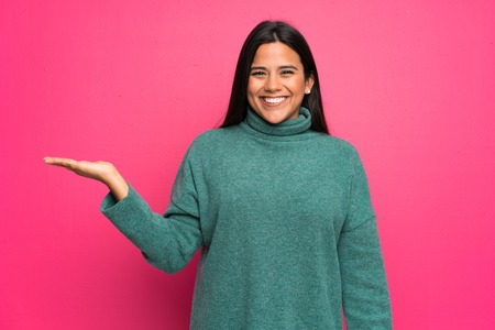 Young Colombian girl with green sweater holding copyspace imaginary on the palm to insert an ad