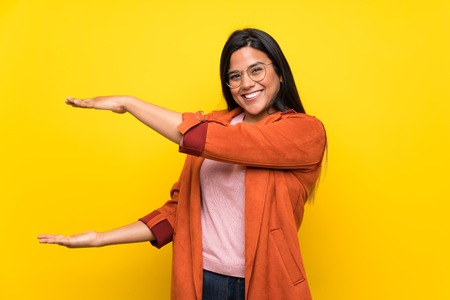 Young Colombian girl over yellow wall holding copyspace to insert an ad
