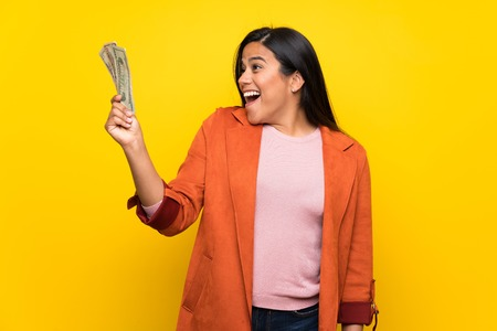 Young Colombian girl over yellow wall taking a lot of money Stock Photo