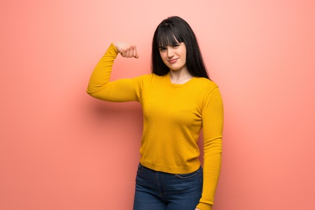 Woman with yellow sweater over pink wall Doing strong gesture Stock Photo