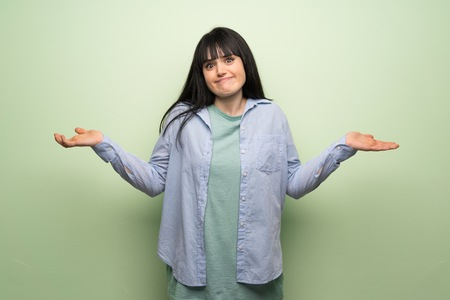 Young woman over green wall having doubts while raising hands and shoulders