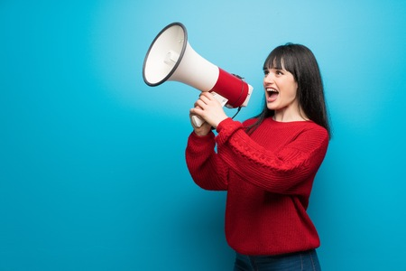 Woman with red sweater over blue wall shouting through a megaphone Imagens