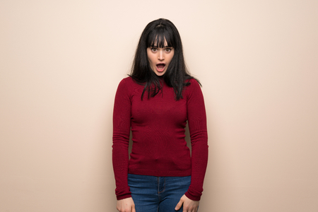Young woman with red turtleneck with surprise and shocked facial expression