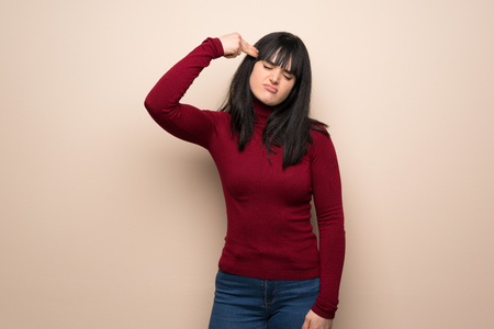 Young woman with red turtleneck with problems making gun gesture