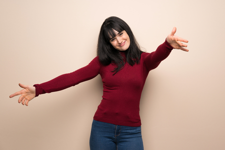 Young woman with red turtleneck presenting and inviting to come with hand
