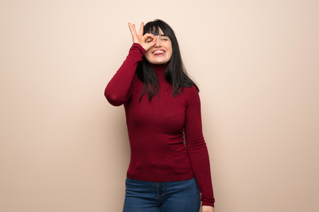 Young woman with red turtleneck makes funny and crazy face emotion Stock Photo