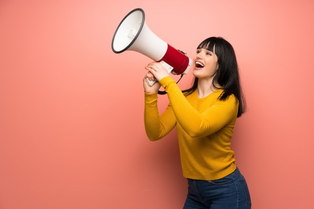Woman with yellow sweater over pink wall shouting through a megaphone Stock Photo