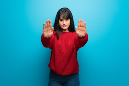 Woman with red sweater over blue wall making stop gesture and disappointed