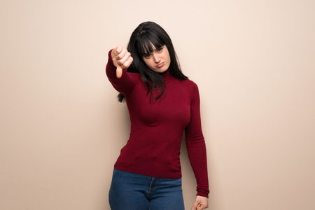 Young woman with red turtleneck showing thumb down sign with negative expression