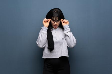 Mujer joven deporte con gafas y sorprendido