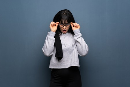Young sport woman with glasses and surprised