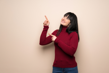 Young woman with red turtleneck pointing with the index finger and looking up Stock Photo