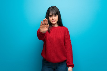 Woman with red sweater over blue wall making stop gesture denying a situation that thinks wrong