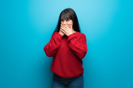 Woman with red sweater over blue wall covering mouth and looking to the side