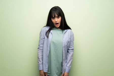 Young woman over green wall with surprise and shocked facial expression