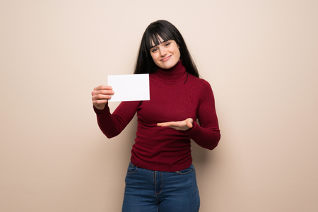 Young woman with red turtleneck holding an empty placard for insert a concept Banque d'images