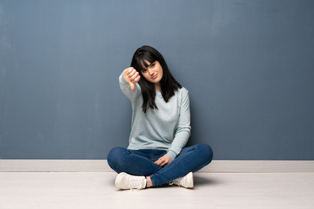 Woman sitting on the floor showing thumb down with negative expression Banco de Imagens