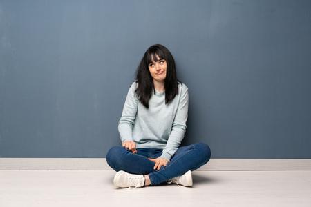 Mujer sentada en el suelo haciendo gesto de dudas mirando de lado