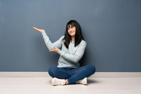 Woman sitting on the floor extending hands to the side for inviting to come