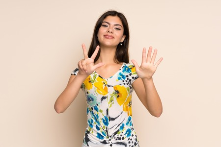 Teenager girl with floral dress counting eight with fingers 스톡 콘텐츠