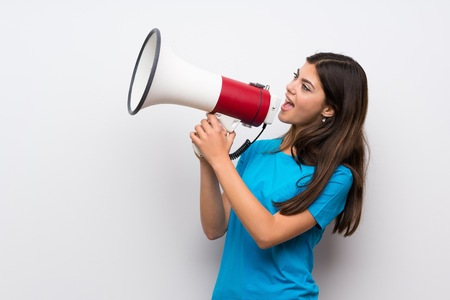 Teenager girl with blue shirt shouting through a megaphone Фото со стока