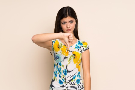 Teenager girl with floral dress showing thumb down with negative expression