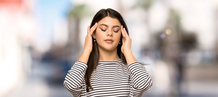 Teenager girl with striped shirt with headache at outdoors