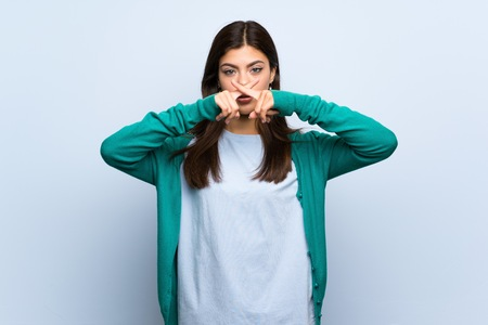 Teenager girl over blue wall showing a sign of silence gesture