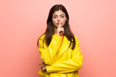 Teenager girl over pink wall showing a sign of silence gesture putting finger in mouth