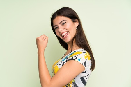 Teenager girl with floral dress celebrating a victory