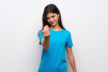 Teenager girl with blue shirt inviting to come with hand. Happy that you came Stock Photo